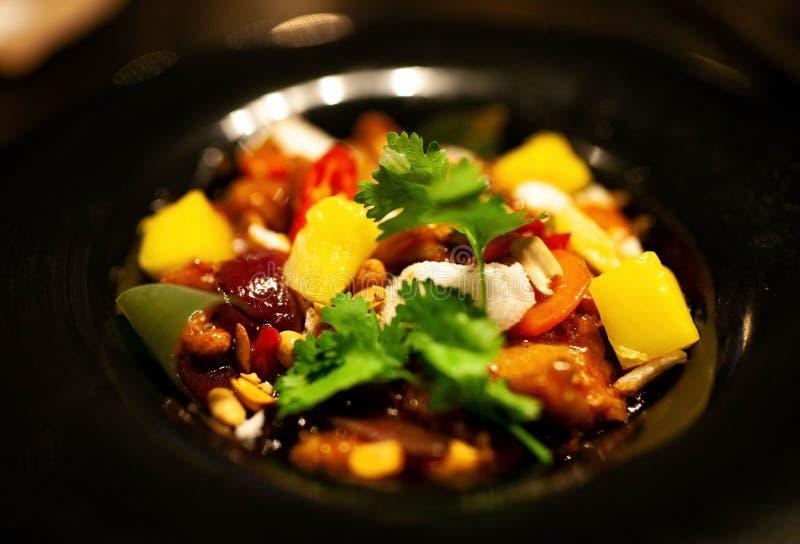 Ali di pollo cinesi con le verdure in salsa agrodolce su un piatto caldo fotografia stock libera da diritti