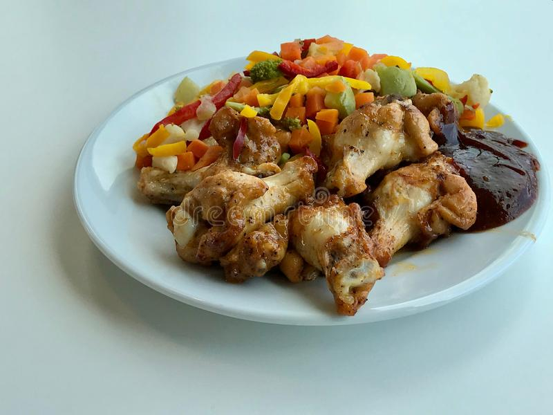 Ali di pollo con salsa barbecue e le verdure pronte da servire con il piatto al ristorante fotografia stock