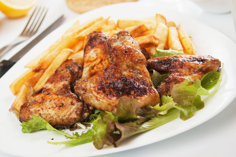 Ali di pollo cotte con le patate fritte immagine stock