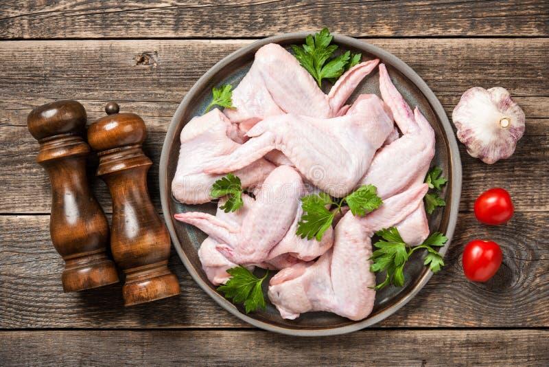 Ali di pollo crude fresche sul piatto e sulle spezie ceramici per cucinare immagine stock libera da diritti