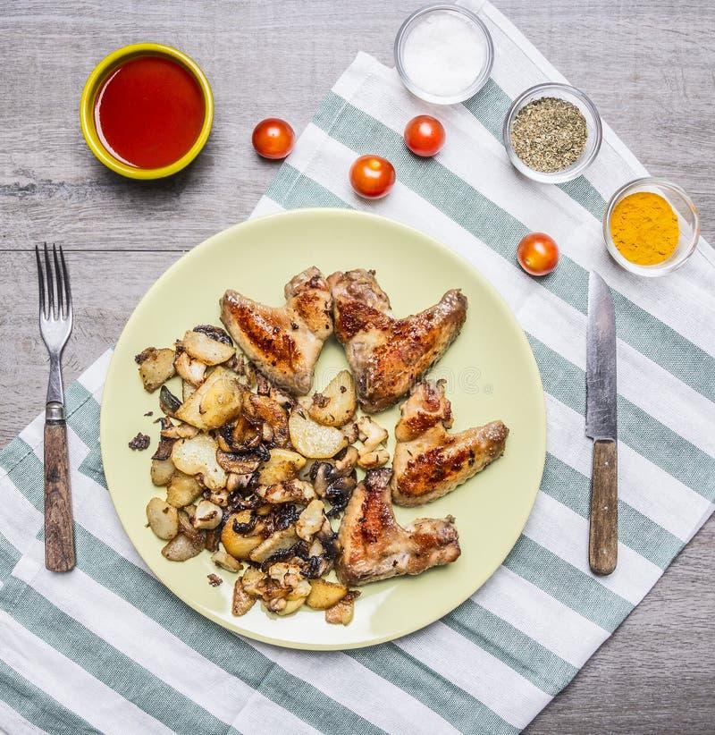 Ali di pollo deliziose fritte con la salsa ed i pomodori ciliegia di peperoncino rosso piccanti fritta delle patate esperti con u fotografie stock
