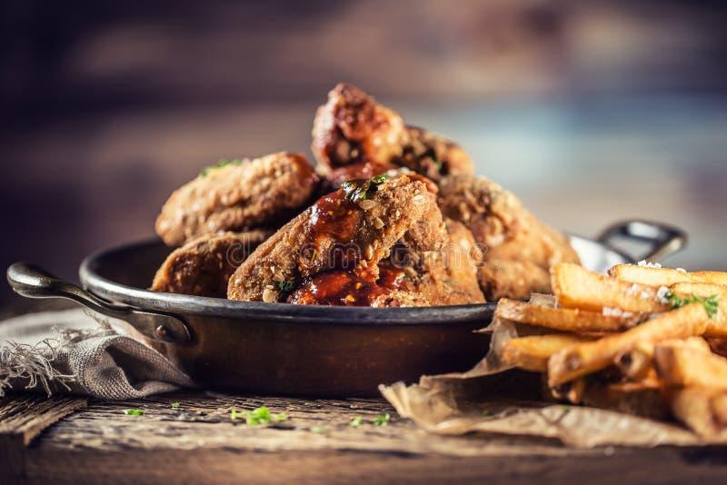 Ali di pollo fritto con le fritture sulla tavola in pub fotografia stock libera da diritti