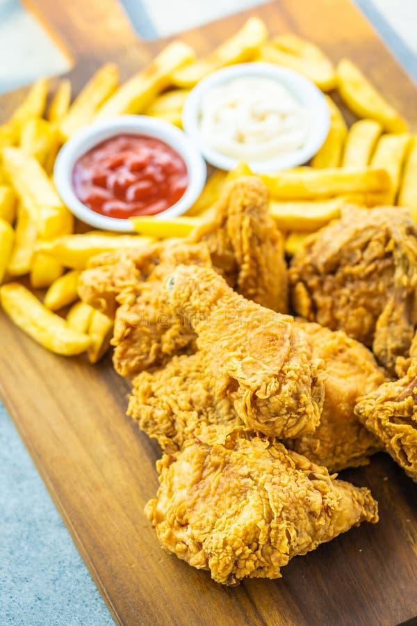 Ali di pollo fritto con le patate fritte e la salsa del pomodoro o del ketchup e della maionese fotografie stock