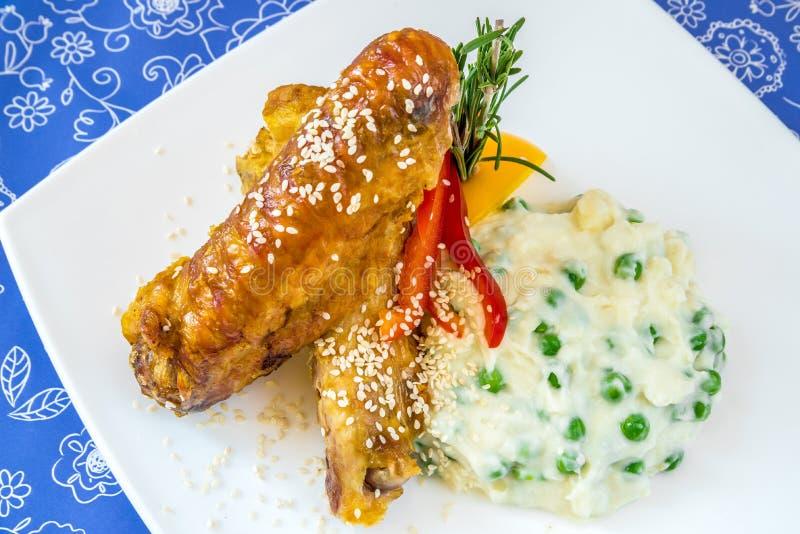 Ali di pollo fritto con le purè di patate, i piselli e le erbe fotografie stock libere da diritti
