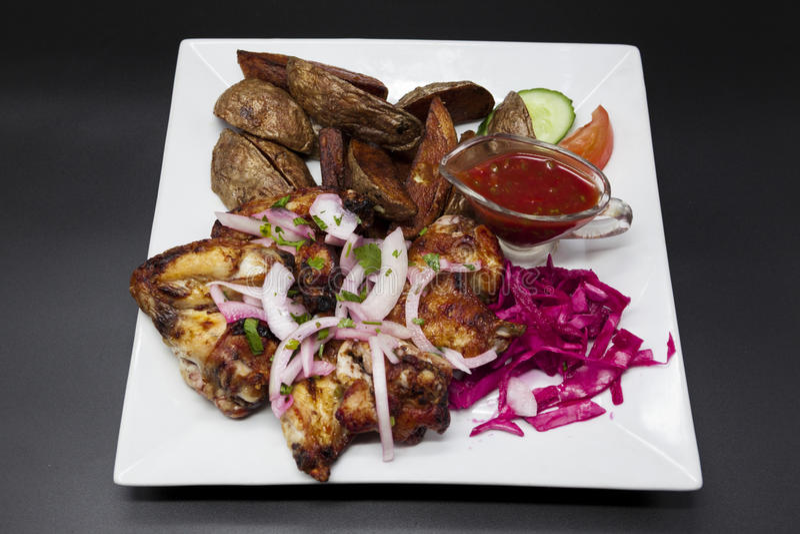 Ali di pollo fritto con salsa piccante, patate su un piatto su fondo nero fotografie stock libere da diritti