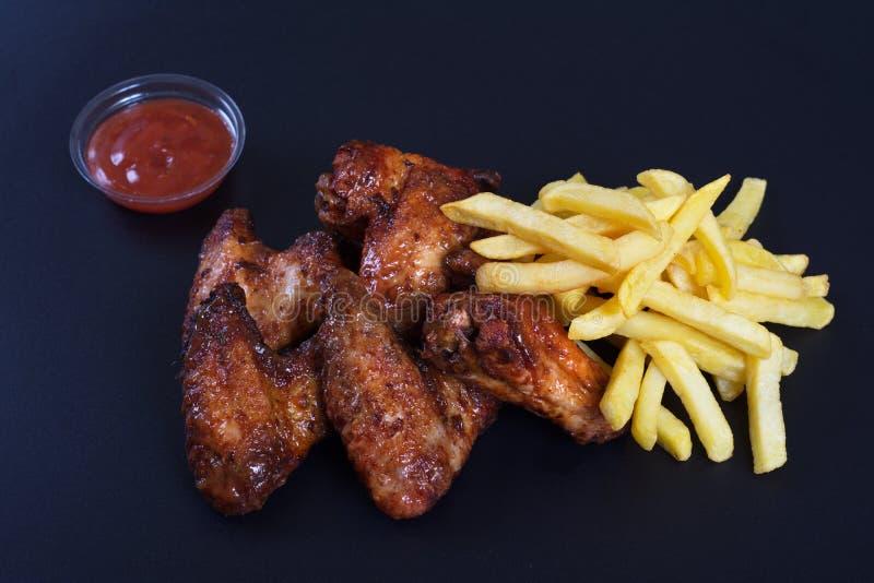Ali di pollo fritto con un piatto laterale delle patate immagini stock