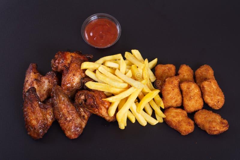 Ali di pollo fritto con un piatto laterale delle patate fotografia stock libera da diritti