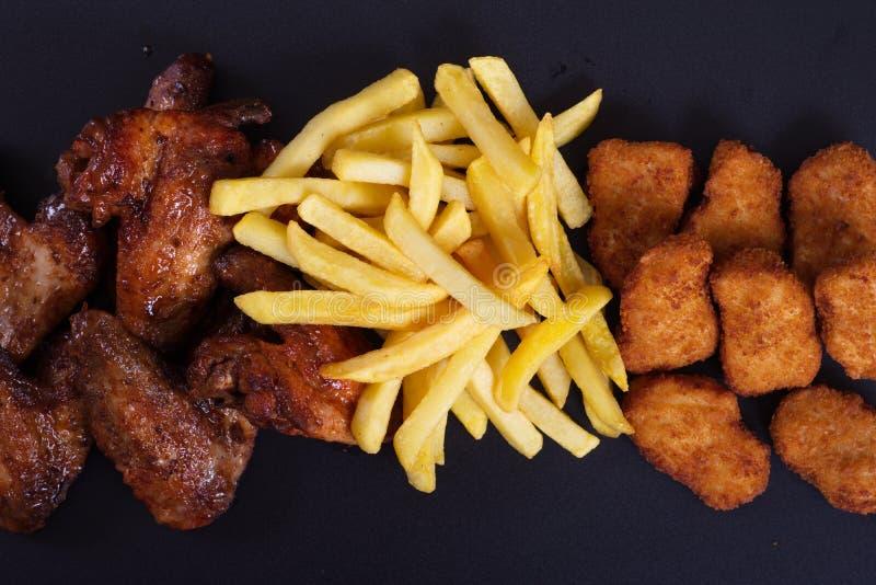 Ali di pollo fritto con un piatto laterale delle patate immagine stock libera da diritti