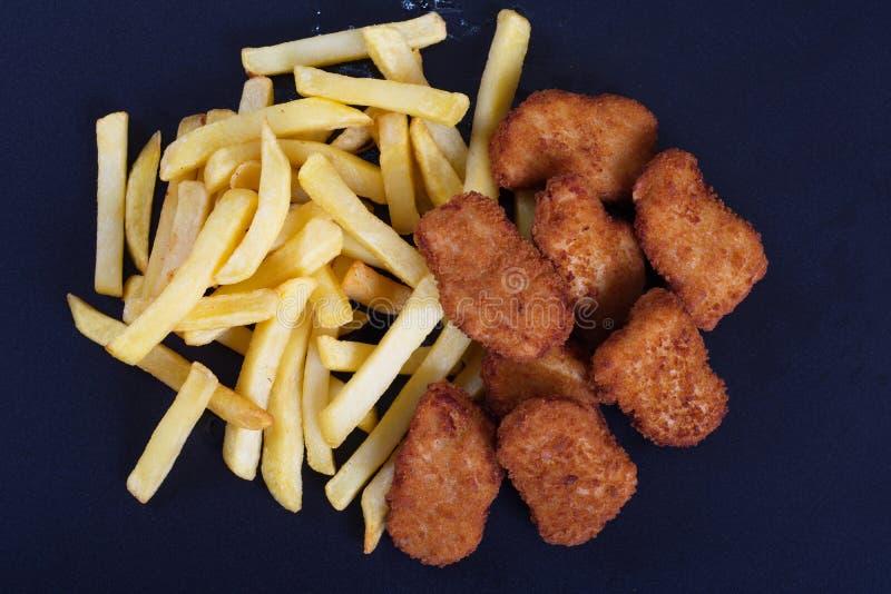 Ali di pollo fritto con un piatto laterale delle patate fotografia stock