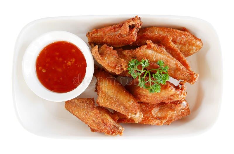 Ali di pollo infornate con salsa nella vista superiore del piatto ceramico isolata su fondo bianco, percorso fotografia stock