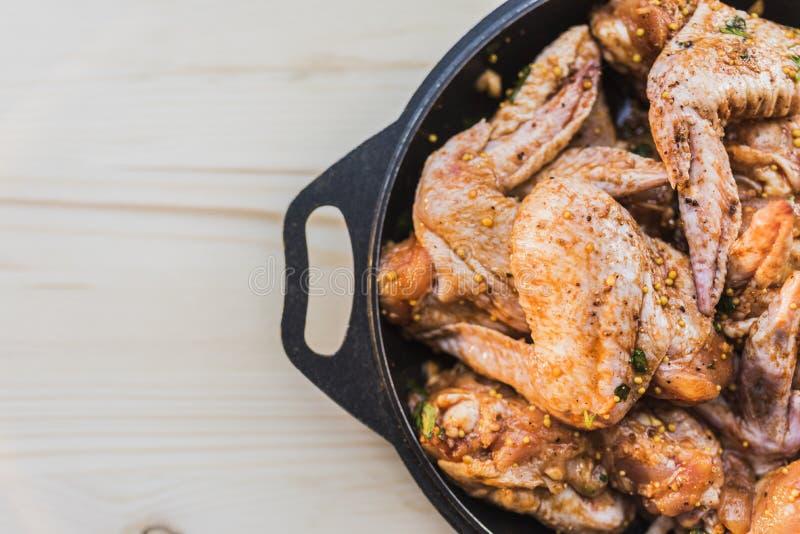 Ali di pollo marinate per grigliare sul lato destro della struttura immagini stock