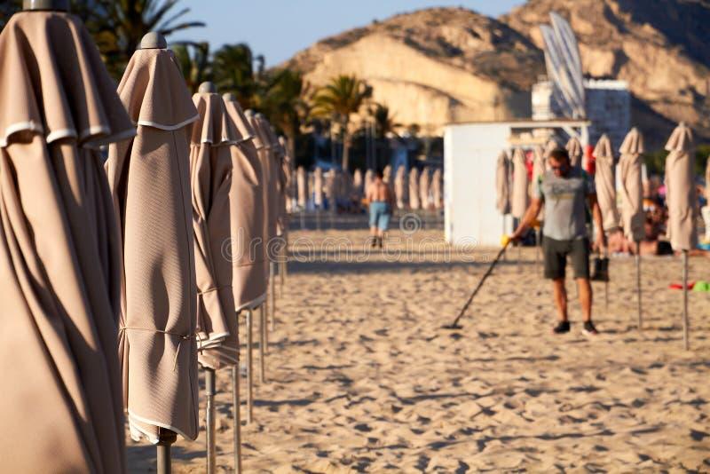 ALIACNTE SPANIEN, CIRCA JULI 2018 män med en metalldetektor på stranden arkivfoton