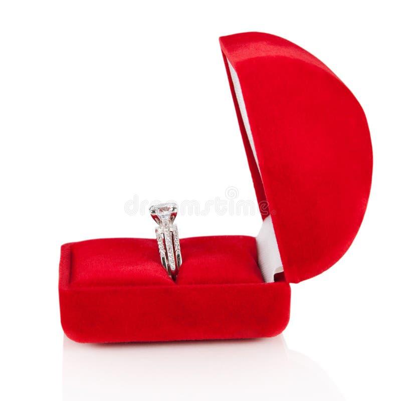 Aliança de casamento luxuosa do diamante na caixa vermelha da seda de veludo fotografia de stock royalty free