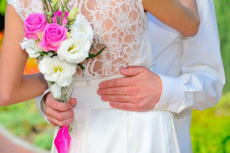 A aliança de casamento: a mão do noivo abraça a cintura da noiva Nós imagem de stock