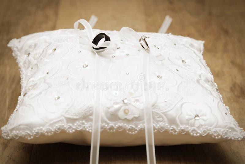 Alianças de casamento amarradas no descanso fotografia de stock