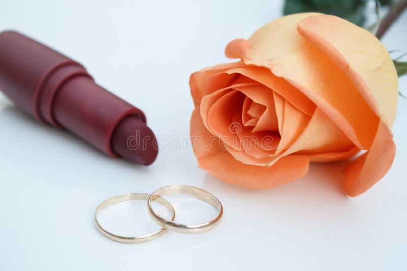 Alianças de casamento, batom e rosa alaranjada, no fundo branco fotografia de stock royalty free