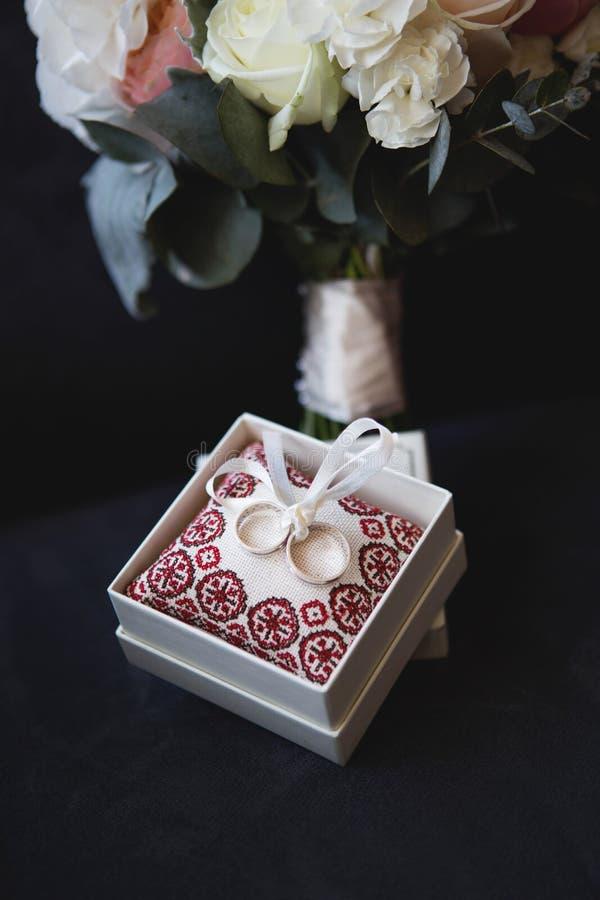 Alianças de casamento bonitas do ouro em uma caixa e em flores fotografia de stock royalty free