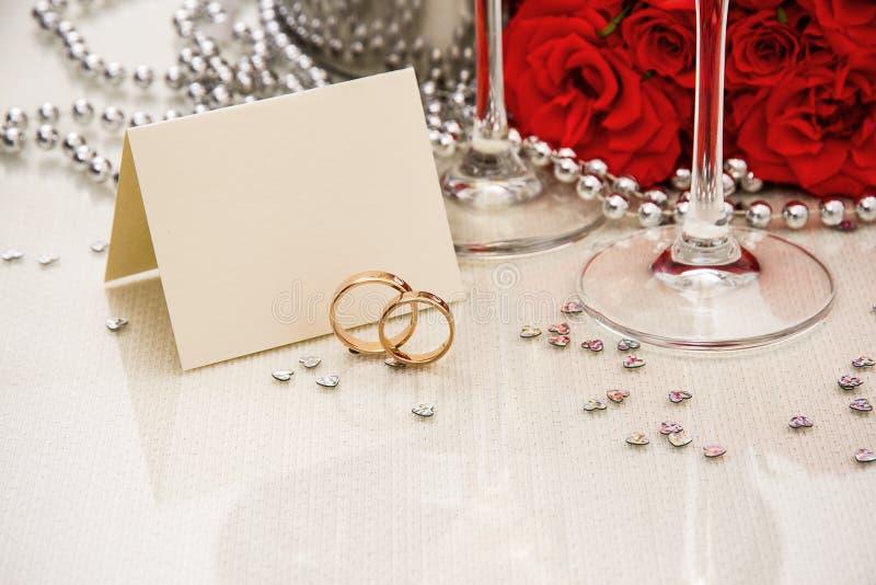 Alianças de casamento com cartão e champanhe da escrita imagens de stock royalty free