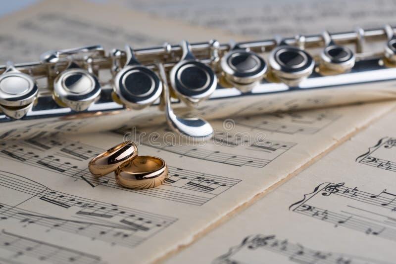 Alianças de casamento com a flauta no fundo velho das notas para o gráfico e o design web, fundo moderno Conceito do Internet tre foto de stock royalty free