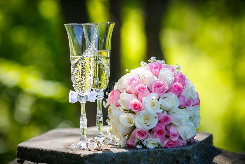 Alianças de casamento com rosas e vidros do champanhe imagem de stock