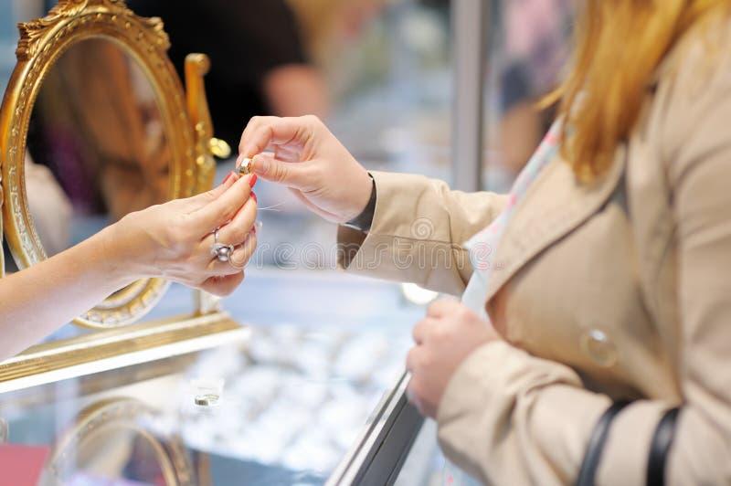 Alianças de casamento de tentativa da mulher em um joalheiro imagens de stock