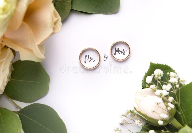 Alianças de casamento do ouro com interior do Sr. e da Sra. texto no branco fotos de stock royalty free