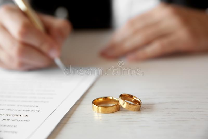 Alianças de casamento douradas na tabela no escritório de notário, imagens de stock