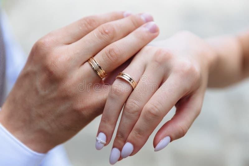 Alianças de casamento douradas nas mãos dos pares imagem de stock
