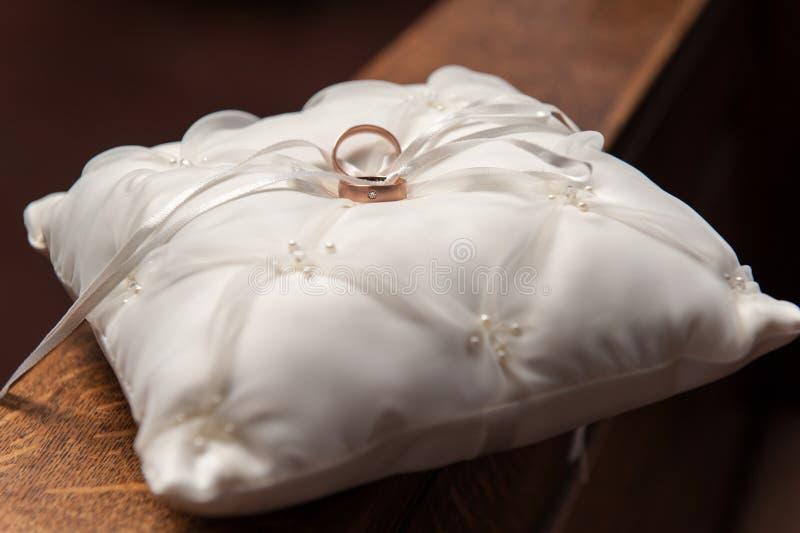 Alianças de casamento douradas no descanso branco do cetim no trilho de mão de madeira imagens de stock