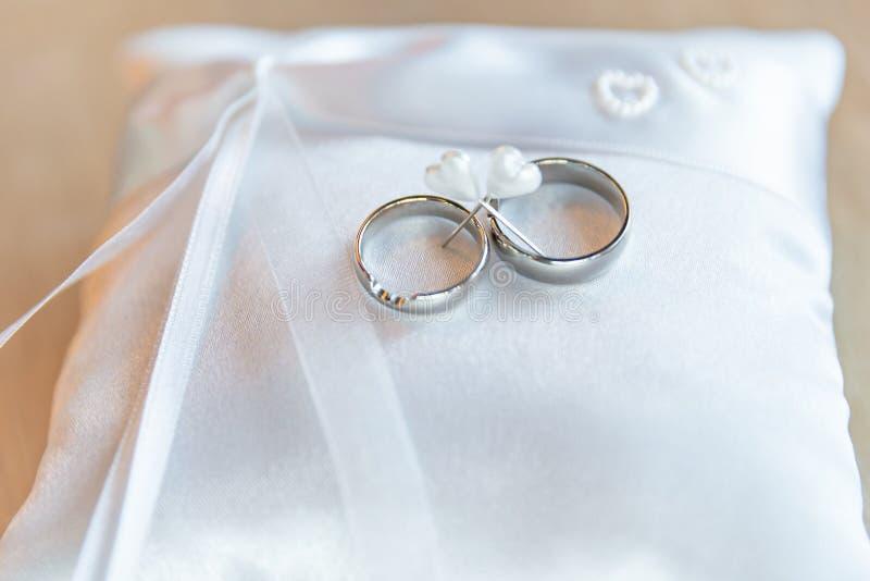 Alianças de casamento douradas no descanso branco pronto para a cerimônia Os recém-casados trocarão seus anéis e dirão sua promes imagem de stock royalty free