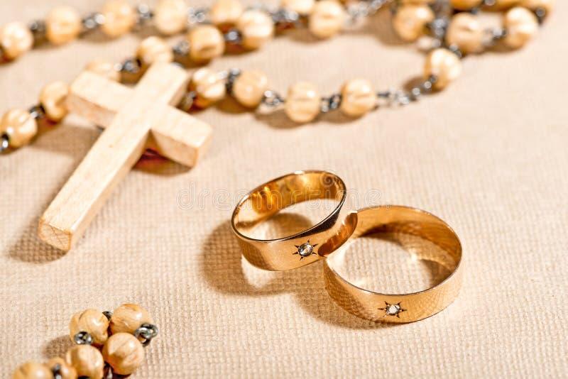 Alianças de casamento e cruz foto de stock