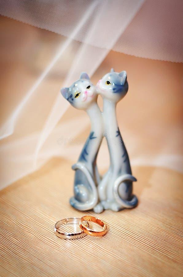 Alianças de casamento e estatueta com gatos imagem de stock