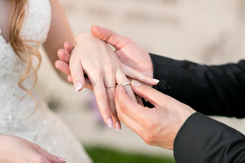 Alianças de casamento e mãos dos noivos pares novos do casamento na cerimônia matrimony Homem e mulher no amor Dois foto de stock