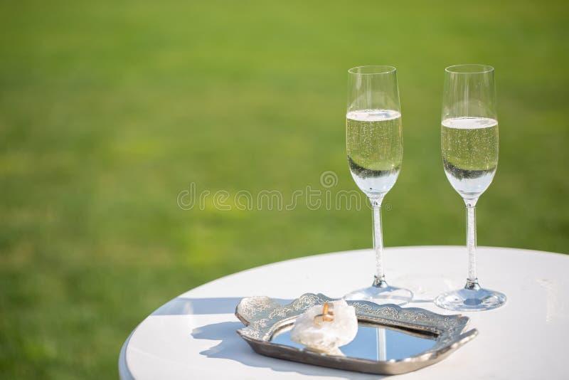 Alianças de casamento e vidros do champanhe foto de stock