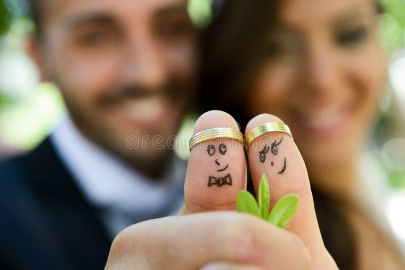 Alianças de casamento em seus dedos pintados com os noivos fotografia de stock royalty free