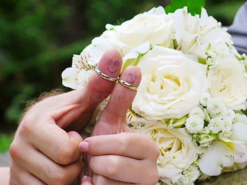 Alianças de casamento em seus noivos dos marrieds dos povos dos dedos, homens pequenos engraçados pintados foto de stock