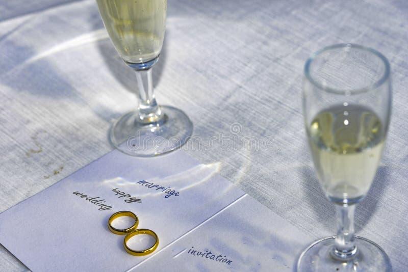 Alianças de casamento em um convite do casamento fotos de stock