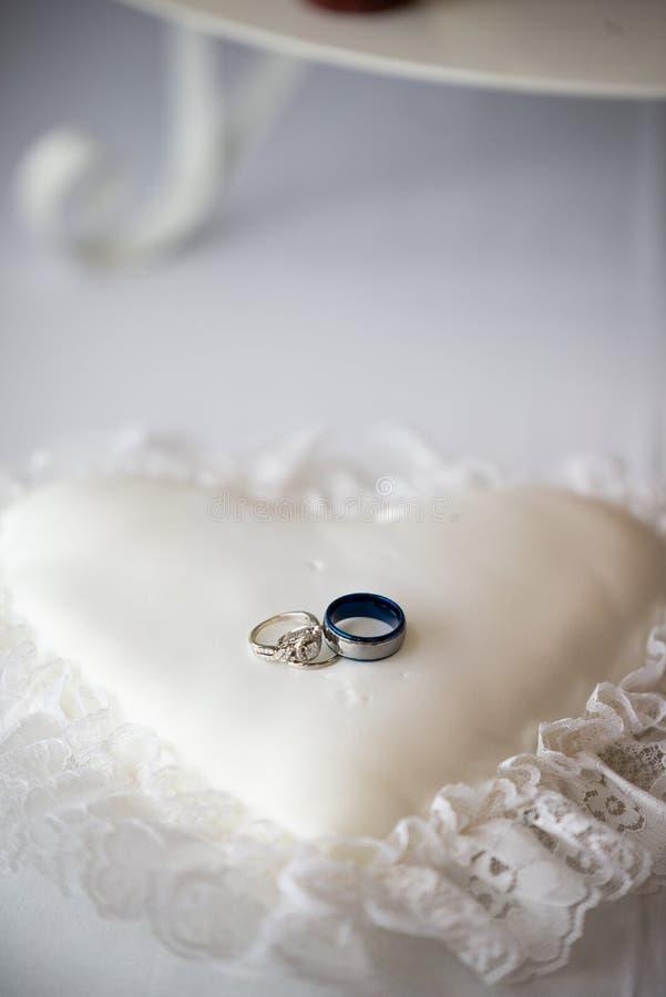 Alianças de casamento em um descanso dado forma coração fotografia de stock royalty free