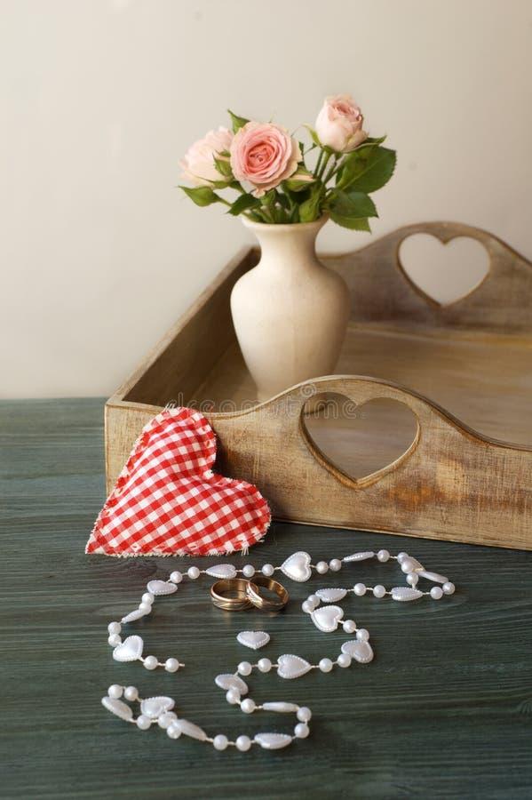 Alianças de casamento em um fundo das flores em um vaso foto de stock
