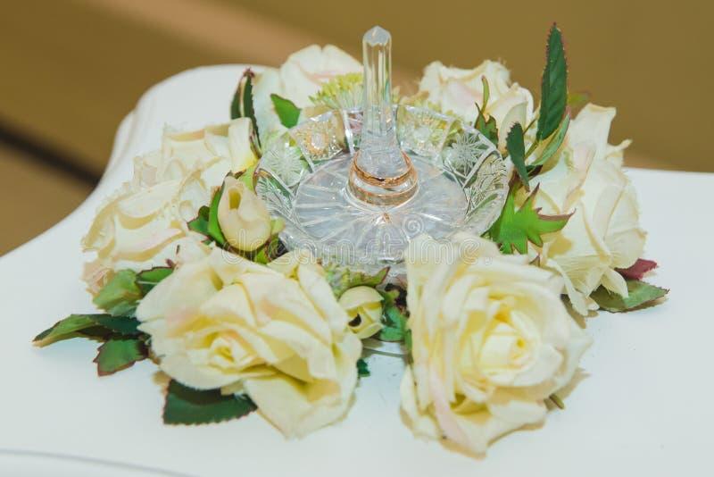 Alianças de casamento em um suporte de cristal das rosas brancas imagem de stock royalty free