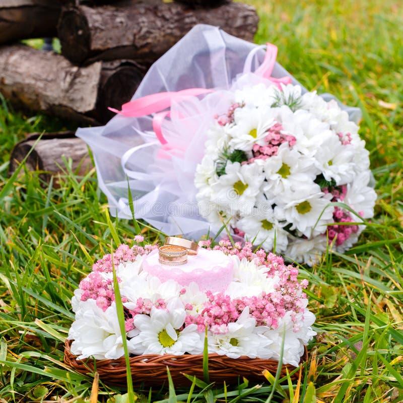 Alianças de casamento em um suporte e em um ramalhete nupcial da camomila branca foto de stock royalty free