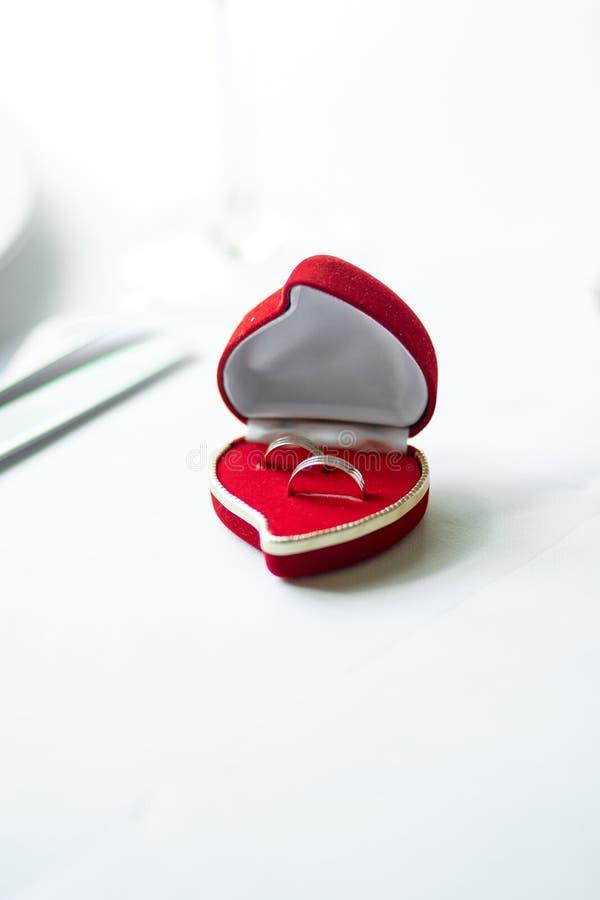 Alianças de casamento em uma caixa coração-dada forma vermelha imagens de stock royalty free