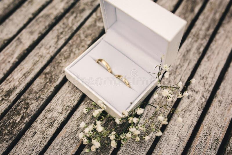 Alianças de casamento em uma caixa na tabela flores pequenas em uma tabela de madeira imagens de stock royalty free
