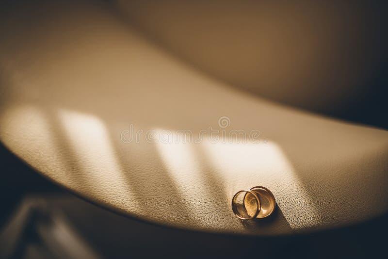 Alianças de casamento em uma poltrona de couro imagens de stock