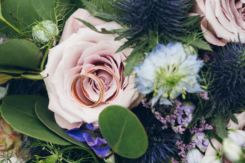 Alianças de casamento em uma rosa no ramalhete do ` s da noiva foto de stock royalty free