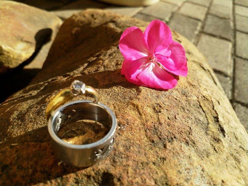 Alianças de casamento em uma superfície da rocha imagens de stock
