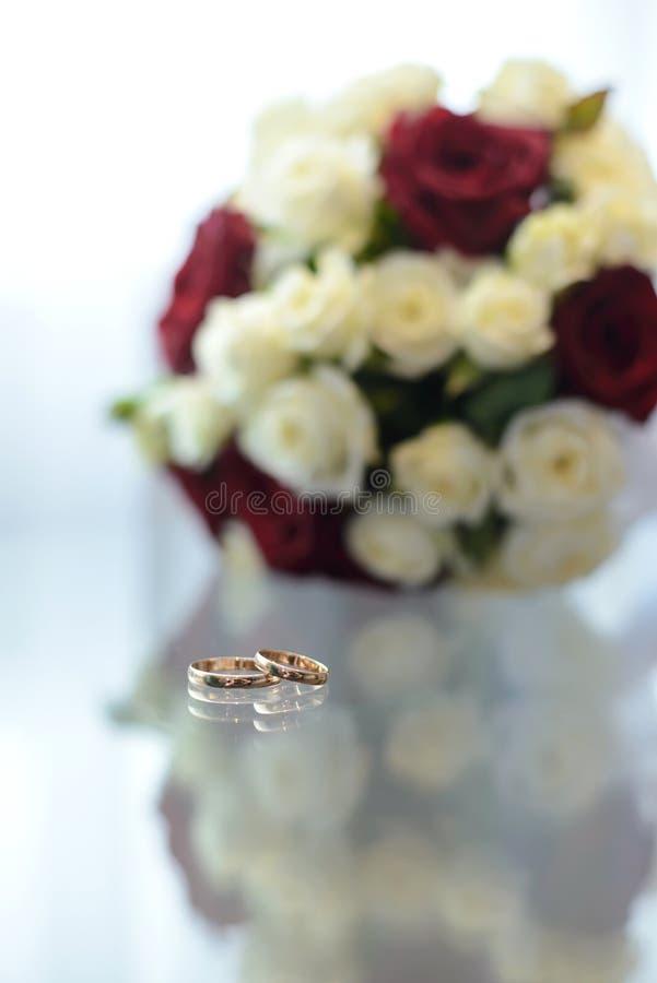 Alianças de casamento em uma tabela de vidro imagens de stock royalty free
