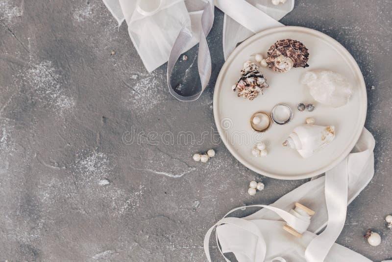 Alianças de casamento lisas no shell, decorações da configuração do conceito do casamento do mar, símbolos do casamento fotos de stock