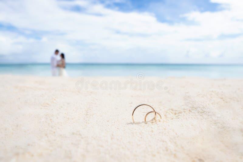 Alianças de casamento na areia branca No fundo os recém-casados e o oceano imagem de stock royalty free