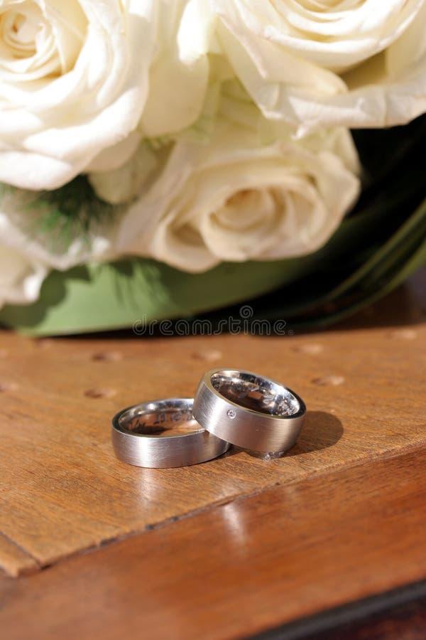 Alianças de casamento na cadeira com rosas brancas fotos de stock royalty free
